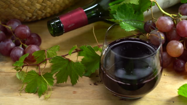 slow motion clip of drop red wine in crystal glass, organic fresh grapes and empty bottle on background, the best of drink in holiday and celebration ideas concept for advertising, free space for text. - fruit juice bottle isolated video stock e b–roll