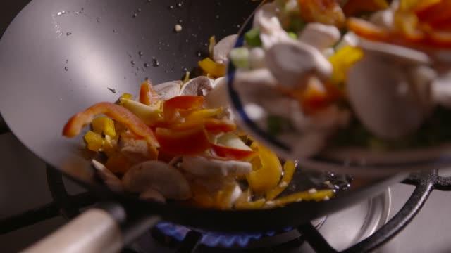 vídeos de stock e filmes b-roll de slow motion clip of sliced vegetables being poured into a wok ready for frying - vinagre