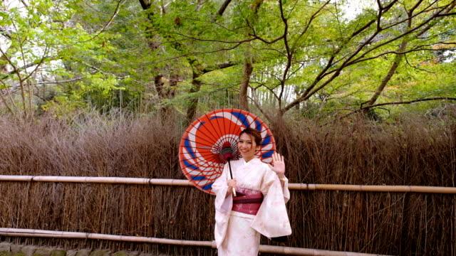 4K Slow Motion Close up : A Asian woman wearing Kimono Dress walking through Bamboo Groves Arashiyama and Sagano. Japanese Culture