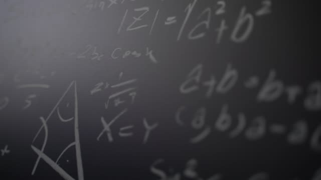 Slow motion close up a math formulas on chalkboard with white chalk.