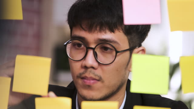 Slow motion close up Asian businessman wear suit looking and writing on sticky note for brainstorming ideas on clear whtieboard at modern office. analyze and synthesis project