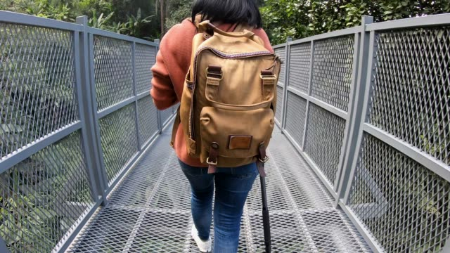 slow motion close up Backpack of asian woman walking on canopy trail in rain forest