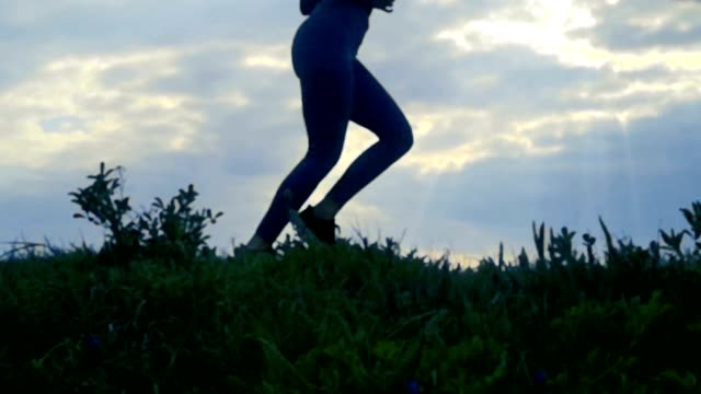 Bидео Slow motion Close Up, Female running at sunrise silhouette background. Girl jogging side view, Tracking shot close up at golden sunrise