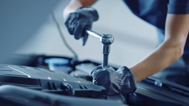 slow motion närbild footage av en professionell mekaniker som arbetar med fordon i bilservice. motor specialist fastställande motor. reparatör bär handskar och använder en ratchet. modern ren verkstad. - maskindel bildbanksvideor och videomaterial från bakom kulisserna