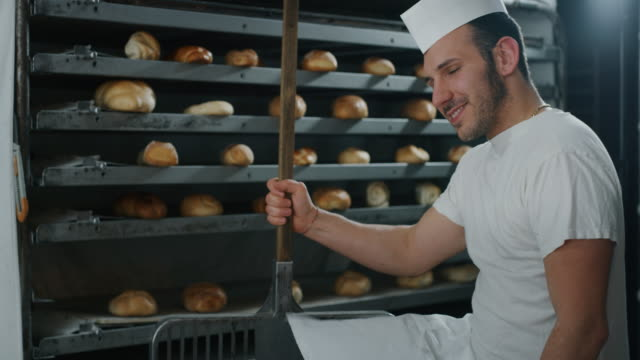 Slow motion close up of a baker pulling out from the oven warm fresh bread just made in a bakery.
