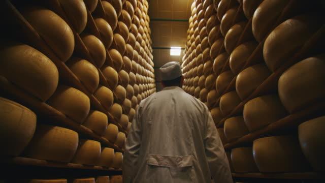치즈 메이커의 슬로우 모션 클로즈업은 수개월 동안 고대 이탈리아 전통에 의해 성숙된 파르메산 치즈의 조미료를 제어하고 있습니다. - 치즈 스톡 비디오 및 b-롤 화면