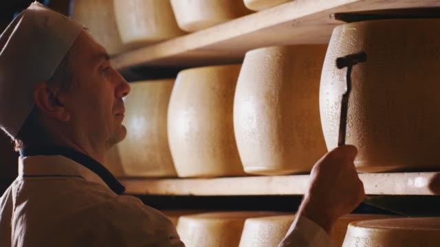 vidéos et rushes de le plan de fermeture au ralenti d'un fromager contrôle l'assaisonnement du fromage parmesan, qui a mûri selon l'ancienne tradition italienne pendant de nombreux mois - parmesan