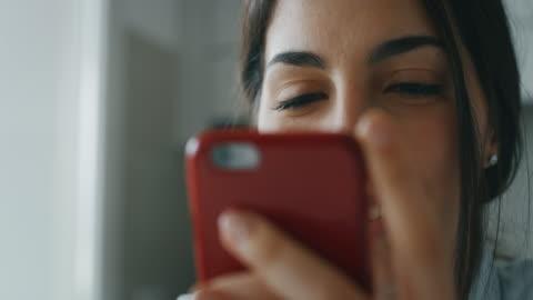 vídeos de stock, filmes e b-roll de câmera lenta de perto de uma jovem sorridente está usando um telefone inteligente durante um café da manhã na cozinha - smartphone