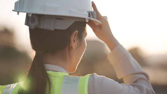 vídeos de stock, filmes e b-roll de close-up em câmera lenta de uma engenheira mulher colocando um capacete de construção ao pôr do sol, sucesso, trabalho e engenharia concept. - engenheiro