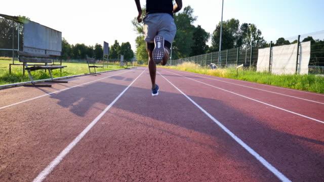 il primo piano al rallentatore di un giovane atleta africano è in corsa in pista nello stadio di atletica leggera in una giornata di sole - atletico video stock e b–roll