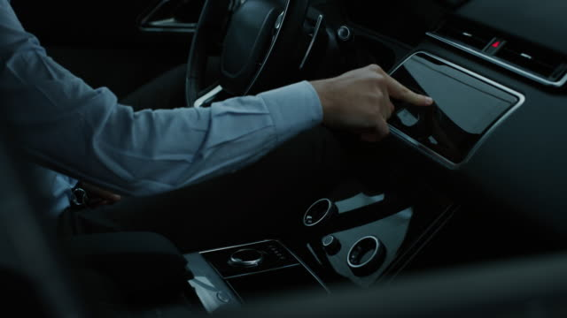 Video Slow motion close up of an young businessman driving a futuristic new technology car with augmented reality holographic display with modern assistance functions.