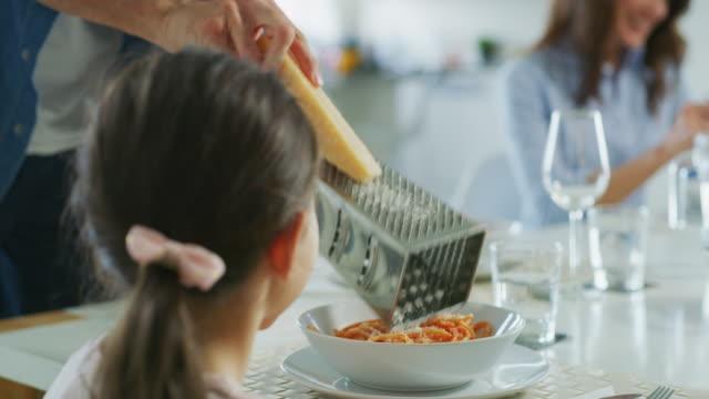 vidéos et rushes de fin de plan lent vers le haut du fromage de râpage de père sur des pâtes italiennes pendant le déjeuner de famille dans la salle à manger. - parmesan