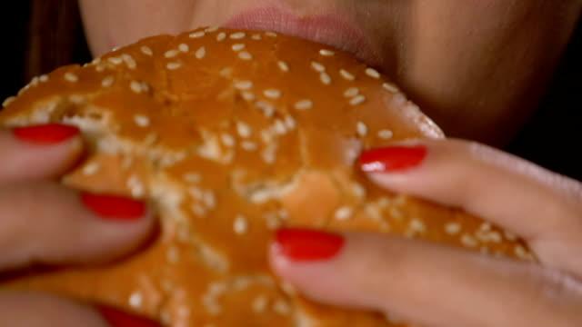 slow motion close up of hungry young woman eating junk unhealthy fast food sandwich hamburger - węglowodan jedzenie filmów i materiałów b-roll