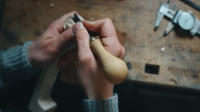 Slow motion close up of master artisan luthier painstaking detailed work on wood violin in a workshop