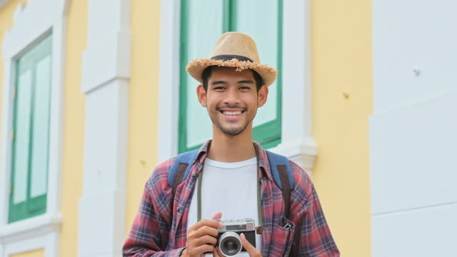 Slow motion close up of young asian man tourist holding camera smiling and looking at camera while travel along the city street, Teenage backpacker traveler on journey in summer vacation in asia