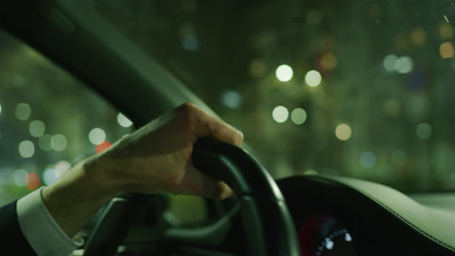 Slow motion close up of young businessman hands driving a modern car in center of the city by night. Slow motion close up of young businessman hands driving a modern car in center of the city by night. Shot in 8K. Concept of business, success, traveling, luxury luxury car stock videos & royalty-free footage