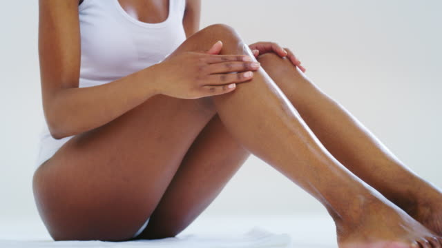Slow motion close up of young dark skin woman with perfect body touching gently her hairless soft and silky legs after depilation isolated on a white background Slow motion close up of young dark skin woman with perfect body touching gently her hairless soft and silky legs after depilation isolated on a white background. serum sample stock videos & royalty-free footage