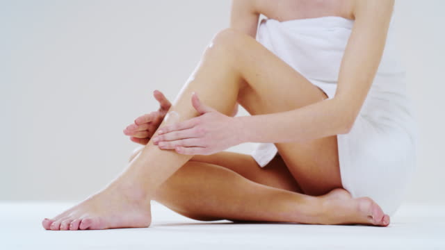 Slow motion close up of young woman with perfect body touching gently her hairless soft and silky legs after depilation isolated on a white background Slow motion close up of young woman with perfect body touching gently her hairless soft and silky legs after depilation isolated on a white background. serum sample stock videos & royalty-free footage