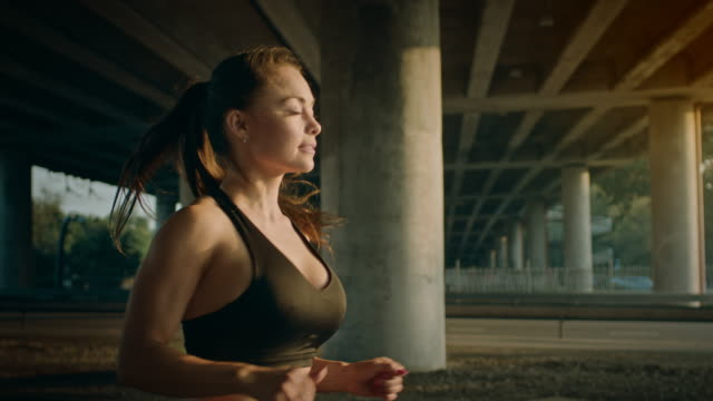 slow motion close up shot of a beautiful fitness girl in black athletic top jogging in a sunny street. she is running in an urban environment under a bridge with cars in the background. - decolleté video stock e b–roll