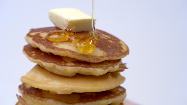 HD Slow motion close up shot pouring honey or maple syrup on stack of homemade fresh hot pancakes with butter on top isolated white background. Delicious sweet food dessert for breakfast.
