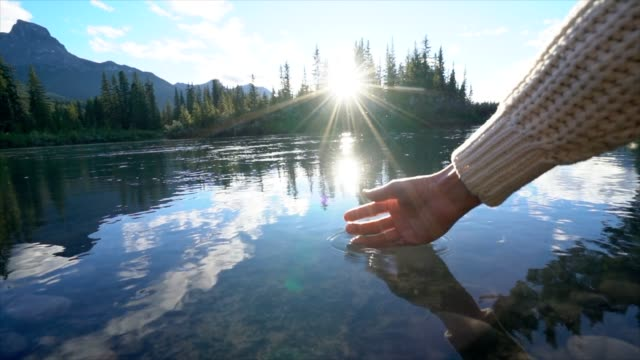 Slow motion,  Closed up on woman's hand trying to get water from river video