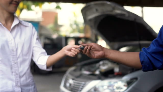 slow motion close-up: hand of young woman send her car key to hand of senior mechanic