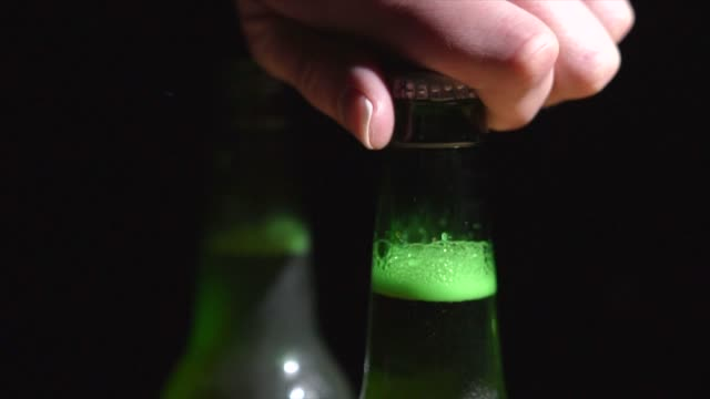slow motion closeup hand twists off beer cap