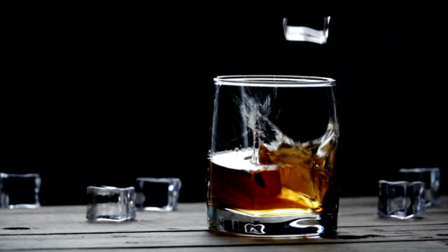 slow motion closeup ice cubes falling into glass - scotch whisky video stock e b–roll