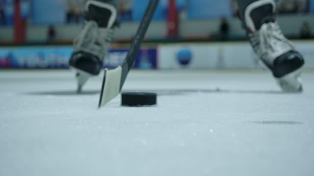 vidéos et rushes de 4k slow motion les joueurs de hockey sur glace s'entraînent à utiliser des bâtons de hockey pour dribbler la rondelle. patinoire de hockey sur glace - hockey sur glace