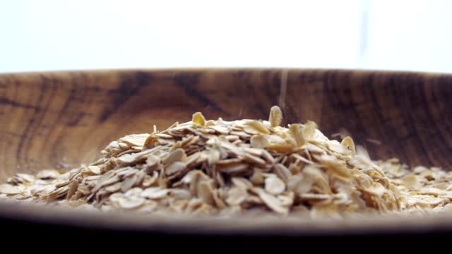 vídeos de stock e filmes b-roll de slow motion closeup oat flakes falling into bowl - oats