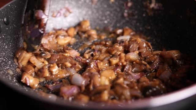 Slow motion closeup of a diced onions and mushrooms gravy being sauteed in a nonstick pan with oil