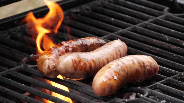Slow motion close-up sausages being cooked on grill