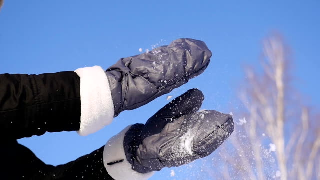 96 FPS slow motion close-up shot of a young girl brushing snow off her mittens video