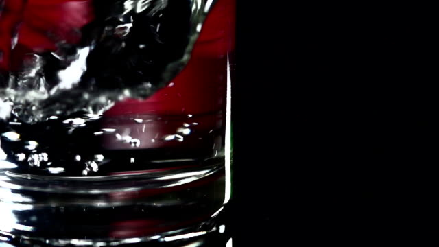 Slow motion, close-up shot of water being poured into a glass tumbler, swirling and creating bubbles. video