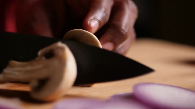 Slow motion closeup sliding or truck shot of a mushroom being chopped with a black chef knife on a cutting board