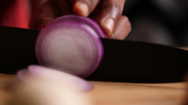 Slow motion closeup sliding or truck shot of a onion being chopped with a black chef knife on a cutting board