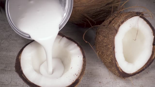 Slow motion coconut milk and coconut halves Slow motion natural thick coconut milk from the cans, pour in half of the coconut coconut stock videos & royalty-free footage