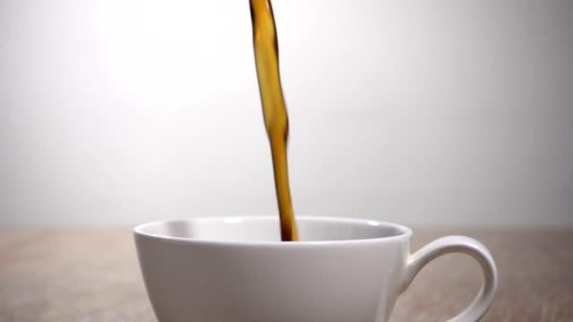 zeitlupe: kaffee gießt in eine tasse - kaffeetasse stock-videos und b-roll-filmmaterial