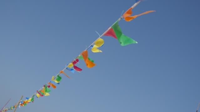 vídeos de stock, filmes e b-roll de corda de controle de multidão lenta galhardete colorido bandeira contra o céu azul - insígnia