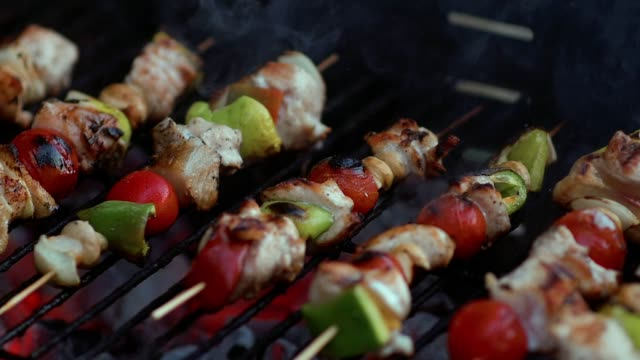 Slow Motion Cooking Fresh Vegetables And Marinated Meat On Bamboo Sticks On Barbecue Grill With Fire And Smoking Closeup