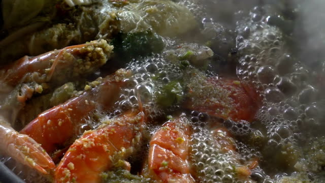 Slow motion: Cooking of spicy seafood soup hot pot