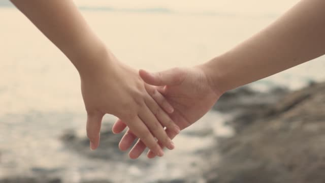 slow motion couple women and men join hands on the beach to feel warm. romantic and loving  .as background valentine concept with copy spaces for your text or design. - mano donna dita unite video stock e b–roll