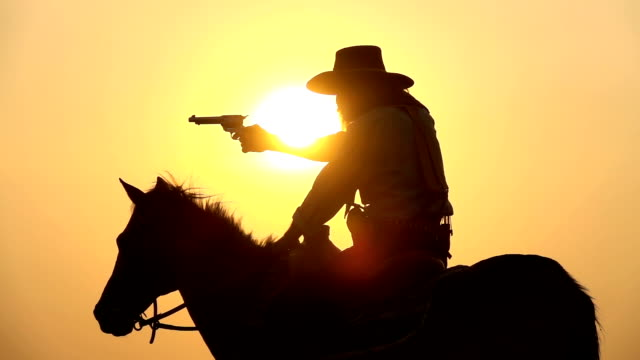 Slow Motion Cowboy Riding Horse And Drawing A Gun At Sunset
