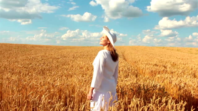 Slow Motion: Crane Shot Of Young Woman In Wheat Field video