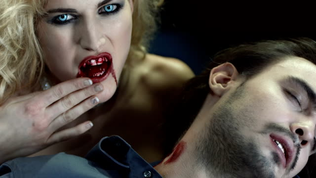 HD Slow Motion: Cruel Vampire Woman Bitting A Man HD1080p: Slow Motion portrait of seductive vampire woman cleaning the blood of her face after bitting a handsome man and turning him into vampire. Recorded at 96 fps vampire stock videos & royalty-free footage