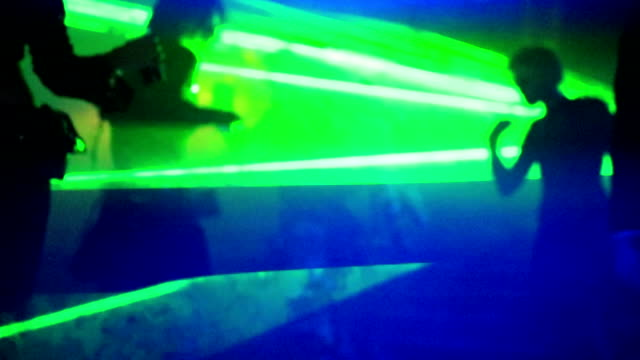 Slow motion dancing Slow motion of people in black dress, daincing in the dark fog with green laser lights. Entertainment, leisure and nightlife concept. Adult lifestyle. organized group stock videos & royalty-free footage