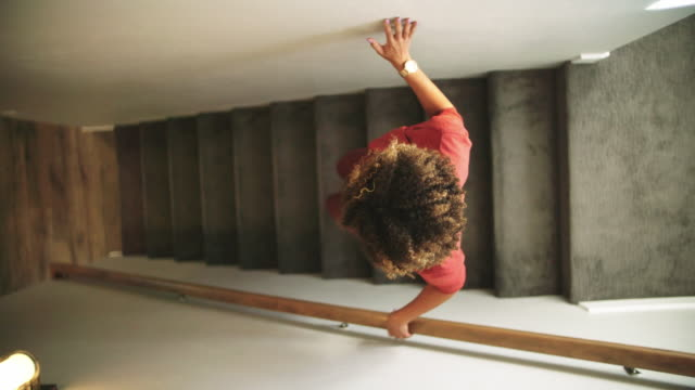 slow motion directly above shot of a woman of mixed race walking down carpeted stairs in a home, using the wall and a hand rail for support - scendere video stock e b–roll
