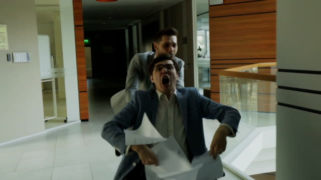 vídeos de stock, filmes e b-roll de câmera lenta zorra tiro de dois empresários loucos andando de cadeira de escritório e jornais a vomitar enquanto se diverte no átrio do centro de negócios moderno - festa da empresa