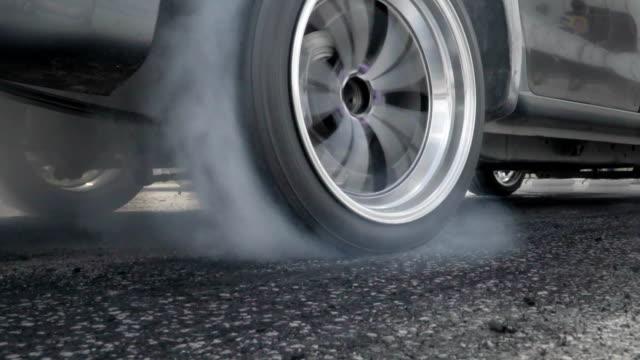 slow motion, dragracing bil bränna däck på startlinjen - på gränsen bildbanksvideor och videomaterial från bakom kulisserna