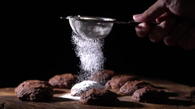 vídeos de stock e filmes b-roll de slow motion dressing one chocolate cookie with icing - bolachas